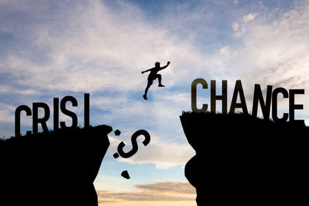 Mindset concept ,Silhouette man jumping from crisis to chance  wording on cliff with cloud sky and sunlight.