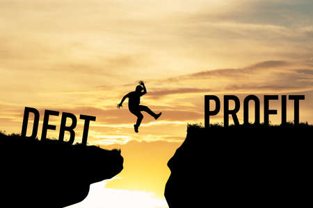 Businessman jumping over two cliffs between debt and profit. It is symbol of business investment target concept. Фото со стока