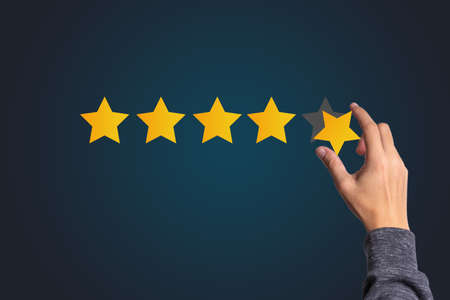 Customer satisfaction and product service evaluation concept , Hand holding and put yellow star to five stars with copy space. Stockfoto