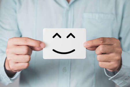 Businessman holding white paperand showing smile or happiness face. Customer satisfaction for product and service concept.