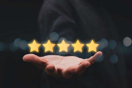 Businessman showing five star on hand for customer evaluation result. Customer satisfaction for product and service concept.