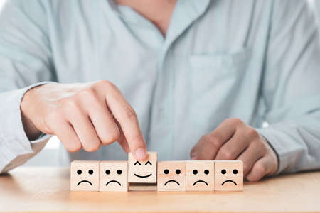 Businessman putting smile face among sad face which print screen on wooden cube block. Emotional management concept.