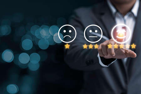 Businessman touching smile face icon for customer online evaluation result for five star. Customer satisfaction for product and service concept.