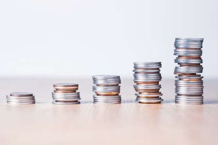 Stock market investment and business profit concept, Increasing Silver and bronze coins stacking chart on table. Stock Photo