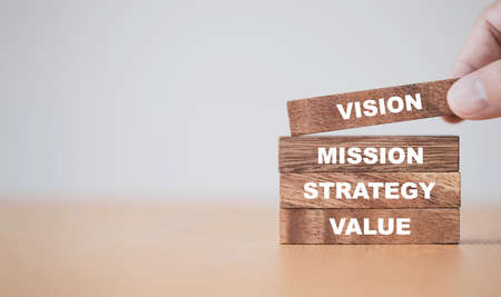 Company key success concept , Hand putting wooden cubes blocks which print screen vision mission strategy and value wording.