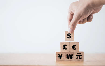 Hand putting US dollar sign on the top of Renminbi Yuan Yen Euro and Pound sterling sign.US dollar is main and popular currency of exchange in the world.Investment and saving concept.
