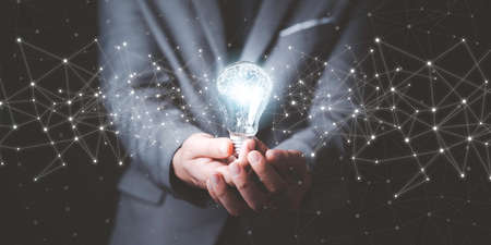 Businessman holding glowing lightbulb with drawing brain and connection line, creative thinking ideas and innovation concept.
