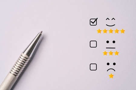 Metallic pen lay down after do customer satisfaction survey  , questionnaire concept. 版權商用圖片