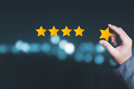 Customer satisfaction and product service evaluation concept , Hand holding and put yellow star to five stars with copy space.