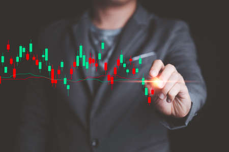 Stock market investment and business growth concept , Businessman trader pointing to stock market investment chart for analysis.
