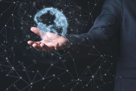 Businessman holding virtual world with connection line for global networks and technology linkage concept.