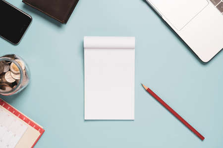 Top view of white blank paper with red pencil laptop and money on blue background table.