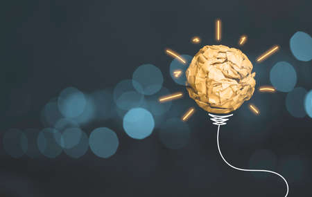 Scrap yellow paper ball with drawing glowing light and wire harness  which sign of lightbulb on blue bokeh background, creative thinking idea and innovation concept.