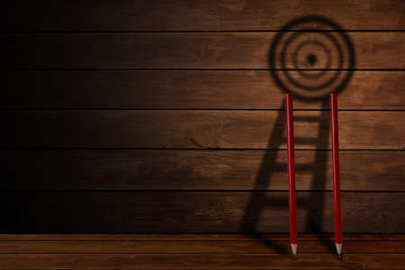 Pencil and stair with target board shadow on wooden background , challenge in business objective achievement and successful concept. 版權商用圖片
