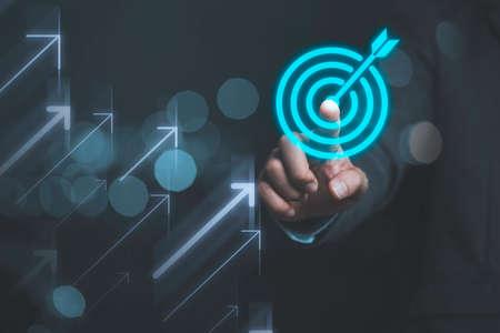 Businessman touching virtual dartboard with arrow ,Business Achievement objective target concept.