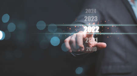 Businessman touching on number 2022 for preparation and change to merry Christmas and happy new year.