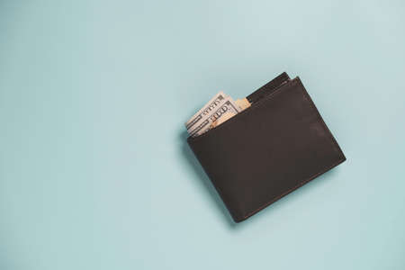 Top view of Brown leather Money wallet with banknote  inside on blue background and copy space.