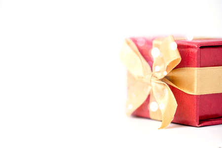 Red gift box and golden ribbon on white and bokeh background, Happy birthday and happy new year concept. 版權商用圖片