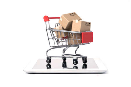 Isolated of Shipping paper boxes inside Red shopping cart trolley on tablet with white background and copy space , Online shopping and e-commerce concept. 版權商用圖片