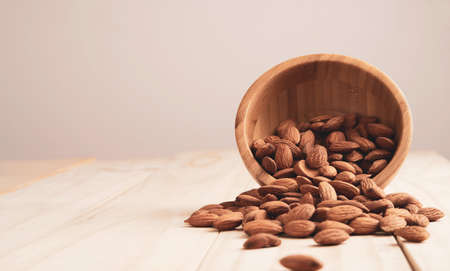 Almonds nut in wooden bowl and pour on table with copy space. Almonds nut is healthy diet food which high protein low fat and essential amino acid.