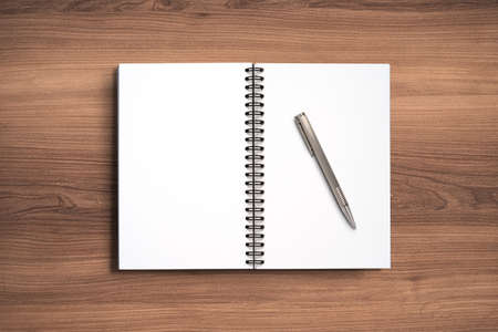 Top view Minimal design of open Notebook with pen on wooden background.