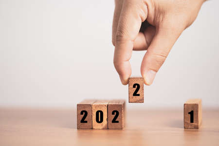 Hand putting number two for replace number one  to change 2021 to 2022 year. Merry Christmas and happy new year concept.
