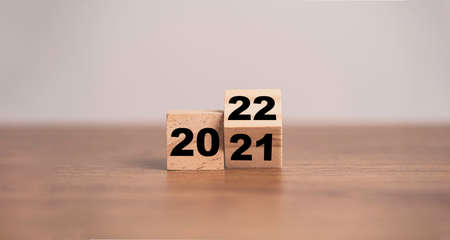 Flipping of wooden cubes block to change 2021 to 2022 year. Merry Christmas and happy new year concept. 스톡 콘텐츠