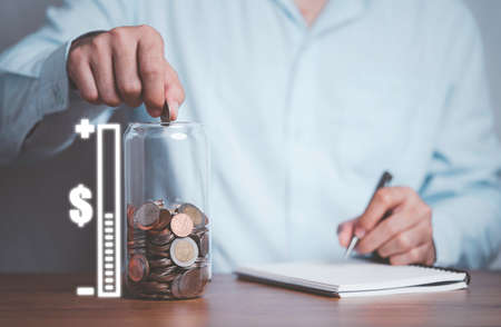 Businessman putting coin and recording  to money saving jar with amount virtual scale of saving for future.