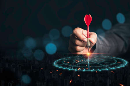 Businessman throwing red arrow dart to virtual target dart board. Setup objectives and target for business investment concept. 스톡 콘텐츠