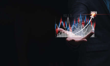 Businessman holding virtual stock market chart and graph for analysis , Value investment and trading concept. 스톡 콘텐츠