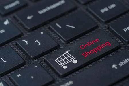 Shopping trolley cart icon and online shopping wording print screen on black laptop computer keyboard.