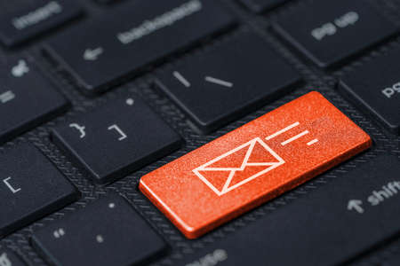 White letter icon print screen on orange button laptop computer keyboard, business contact and information concept. 스톡 콘텐츠