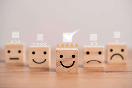 Customer satisfaction survey concept, human face icons print screen on wooden cube block with stars and mark for evaluate product and service.