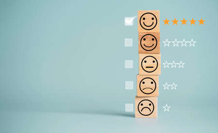 Customer satisfaction survey concept, human face icons print screen on wooden cube block with stars and mark on blue background for evaluate product and service.
