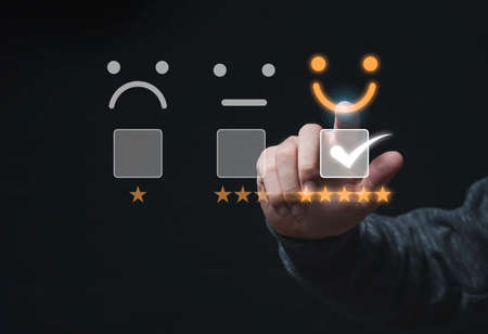 Customer satisfaction survey concept, Businessman touching smiley face icon with yellow five stars and correct mark to evaluate product and service.