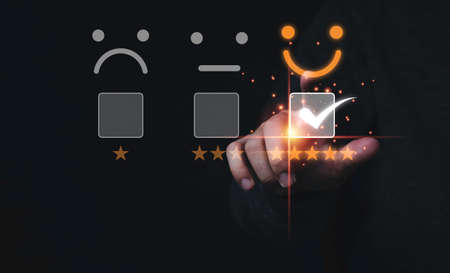 Customer satisfaction survey concept, Businessman touching smiley face icon with yellow five stars and correct mark to evaluate product and service. 스톡 콘텐츠