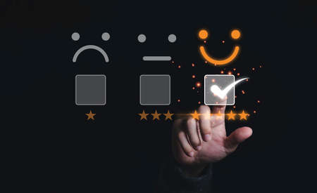 Businessman touching and doing mark to select smiley face with five yellow stars on black background, the best customer satisfaction and evaluation for good quality product and service.