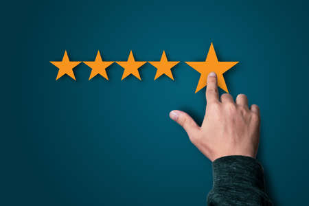 Businessman touching to five yellow stars on dark blue background, the best customer satisfaction and evaluation for good quality product and service.