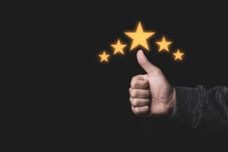 Hand and thumb rise up with five yellow stars on black background, the best customer satisfaction and evaluation for good quality product and service.