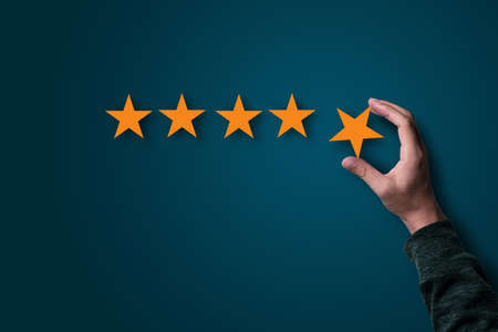 Hand holding and putting yellow stars for evaluate quality of product and service , customer satisfaction concept.