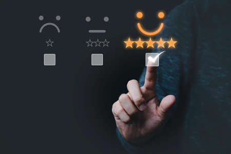 Hand touching and doing mark to select smiley face icon for evaluate product and service, customer satisfaction concept.