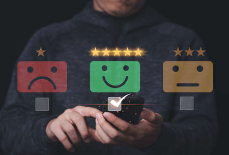 Businessman using mobile and touching to smiley face for customer survey product and service , Customer satisfaction and evaluation concept.