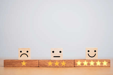 Customer satisfaction survey concept, human face icons and yellow stars print screen on wooden cube block on table for evaluate product and service.
