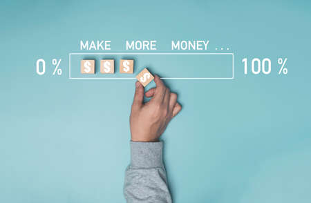 Businessman hand putting dollar sign which print screen on wooden cube block on blue background for increase percentage of loading make more money concept.