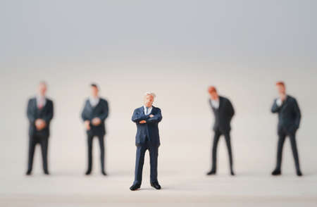 Close-up of miniature figure of one businessman standing out from the crown of others businessmen , Leadership concept.