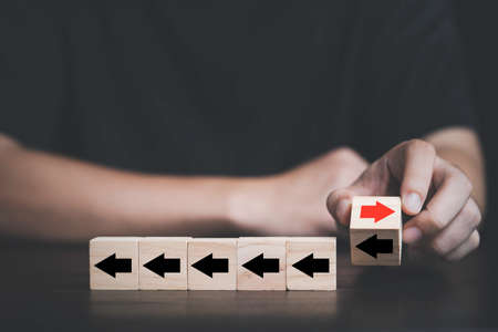 Businessman flipping and change direction of red arrow and black which print screen on wooden cube block , Technology and business disruption concept.