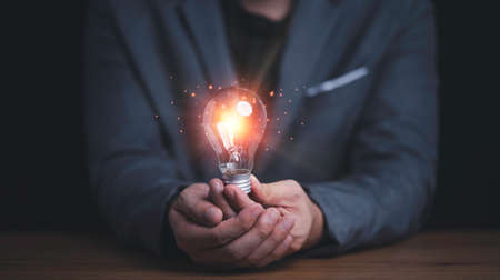 Businessman holding connection of light bulb with orange ray , Creative thinking idea and innovation concept.