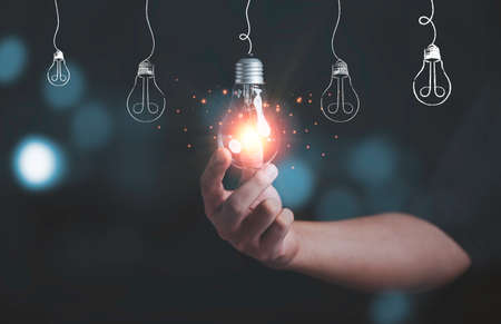 Businessman holding glowing lightbulb with light ray for creative thinking ideas and innovation concept.