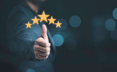 Businessman hand thumb rise up with yellow stars for customer satisfaction and product service evaluation concept.