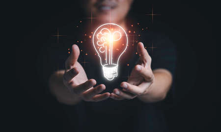 Man hand holding hanging glowing drawing light bulb with orange rays , creative thinking idea and innovation concept.